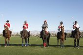 Polo players and umpire mounted on horses on field
