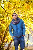 Young man walking in yellow autumn park.