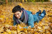 Young dreaming man in autumn park.