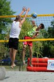 KAPOSVAR, HUNGARY - AUGUST 4: Bence Bozoki (in white) in action at a ROAK Viragfurdo Kupa beach volleyball competition, August 4, 2013 in Kaposvar, Hungary.