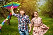 Happy couple are fling  kite on a spring meadow