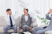 Businessmen shocked at colleague screaming and throwing papers on the sofa in office