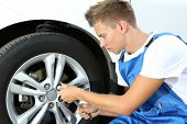 Auto mechanic changing wheel