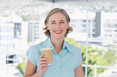 Businesswoman holding disposable coffee cup smiling at camera