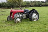 vintage style 1940's tractor in a farmyard on the grass