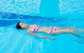 An Asian Girl Is Swimming Backstroke In The Swimming Pool