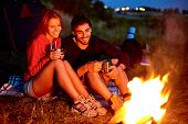 stock photo of firewood  - Young couple sitting on the ground and drinking tea while looking at fire - JPG