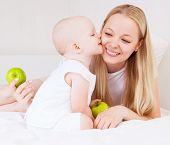 young mother and baby eating apples in bed at home