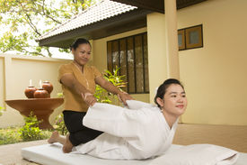 stock photo of thai massage  - Woman getting Thai massage from professional masseuse - JPG