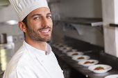 Cheerful young chef smiling at camera in a commercial kitchen