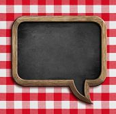 stock photo of lunch  - menu chalkboard speech bubble on table with picnic tablecloth - JPG