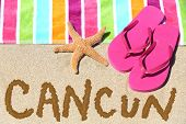 Cancun, Mexico beach travel concept. CANCUN written in sand with water next to beach towel, summer sandals and starfish. Summer and sun vacation holidays.