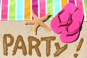 Beach party travel fun concept. PARTY written in sand with water next to beach towel, summer sandals and starfish. Summer and sun vacation holidays background.