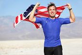Success - winning runner cheering with USA flag celebrating victory. Fit American male winner fitnes