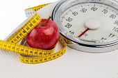 on a personal scale is an apple. symbolic photo for weight loss and healthy, vitamin-rich diet.