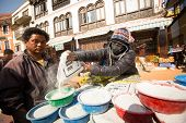 KHATMANDU, NEPAL - DEC 17, 2013: Unidentified man sell cement for donations for repairs near stupa B