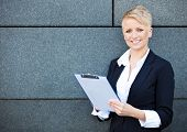 Confident businesswoman holding clipboard