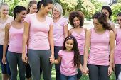 Group of women with girl supporting breast cancer campaign in park