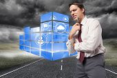 Thoughtful businessman holding pen to chin against cityscape on stormy landscape background