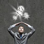 Young businessman Holding arms above head. Money concept