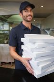 Happy pizza delivery man holding many pizza boxes in a commercial kitchen