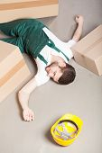 stock photo of workplace accident  - Wounded warehouse worker lying unconscious on the floor after accident - JPG