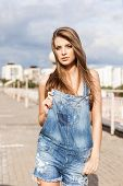 stock photo of overalls  - beautiful girl with long silky hair in denim short overalls holding front part of it - JPG