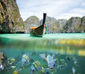 Underwater picture with fish and traditional longtail boat in Maya bay, Ko Phi Phi Le, Tailand