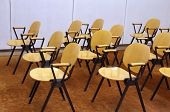Rows of empty wooden yellow chairs in a workshop room