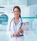 Happy female doctor looking at camera in MRI room of hospital.
