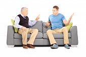 Two men arguing seated on a sofa isolated on white background