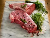raw porterhouse and tenderloin with mixed herbs juniper berry,pepper, salt