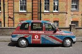 LONDON, ENGLAND - MAY 25: a traditional London taxi covered with Vodafone advertising
