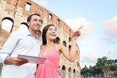 Happy travel couple with tablet by Coliseum, Rome, Italy. Smiling young romantic couple traveling in