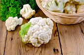 stock photo of wooden basket  - Cauliflower on a table and in a wicker basket dill parsley on wooden board - JPG