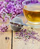image of oregano  - Metal sieve with dried flowers of oregano a herbal tea in a glass cup fresh flowers of oregano on the background of wooden boards - JPG