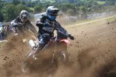 picture of dirt-bike  - Two racing dirt bikes corner in a cloud of mud - JPG