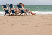 People Relax In Beach Chairs On Florida Beach