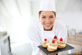 stock photo of pastry chef  - Smiling pastry chef showing desserts on plate - JPG