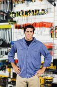 Portrait of confident male customer with hands on hip standing in hardware shop