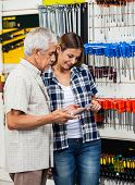 Senior man and daughter looking at wrench while standing in hardware shop