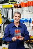 Portrait of confident worker holding screwdriver package in shop