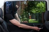 picture of felon  - Horizontal view of burglar opening car door - JPG