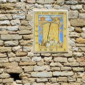 foto of sundial  - Ancient sundial clock on the stone wall of castle Le Barroux Provence France - JPG