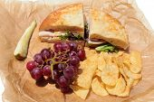 A picnic lunch with a Turkey and Cheese Sandwich on Cheese Bread, Chips, Red Grapes and a Dill Pickl