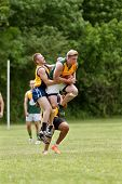 Player Jumps To Catch Ball In Australian Rules Football Game
