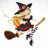 Beautiful witch with candy in pumpkin
