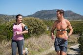 Active couple jogging in the countryside on a sunny day