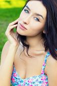 beautiful young sexy sweet girl with blue eyes with long black hair sitting in the Park