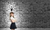 Pretty schoolgirl and light bulb. Idea concept